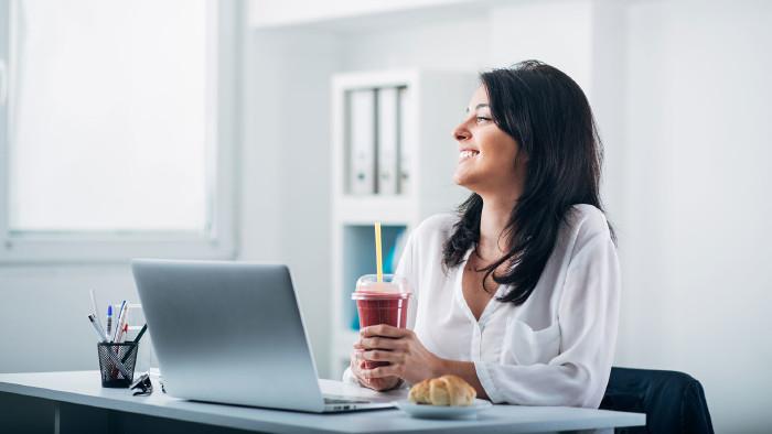 Frau sitzt am Schreibtisch, hält einen Smoothie in der Hand und lacht. Vor ihr steht der Laptop und daneben ein Croissant. © ©Suteren Studio - stock.adobe.com, AK Stmk