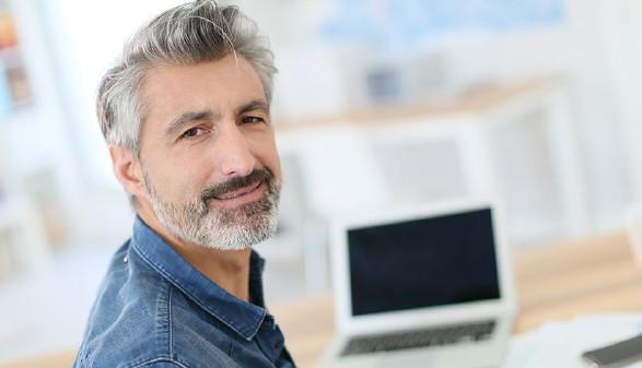 Älterer Mann sitzt am Schreibtisch lächelt in die Kamera. © Fotolia.com/goodluz, AK Stmk