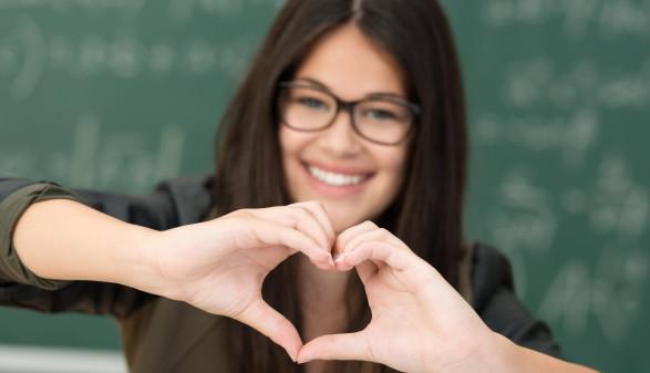 Studentin macht vor der Tafel ein Herz mit den Fingern. © Fotolia/contrastwerkstatt, AK Stmk
