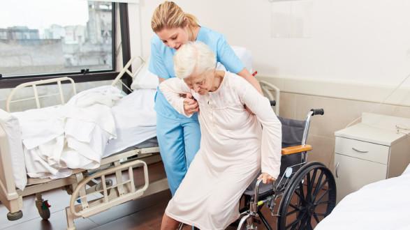Pflegekraft hilft älteren Frau in den Rollstuhl © Robert Kneschke, stock.adobe.com