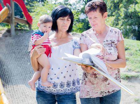 Zwei Kinderbetreuerinnen schauen sich mit einem Kind die AK-Studie an. © Graf, AK Stmk