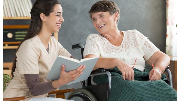 Betreuerin liest Frau im Rollstuhl vor © Katarzyna Bialasiewicz Photographee.eu, fotolia