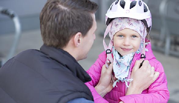Papa setzt Mädchen Kinderfahrradhelm auf. © Graf, AK Stmk