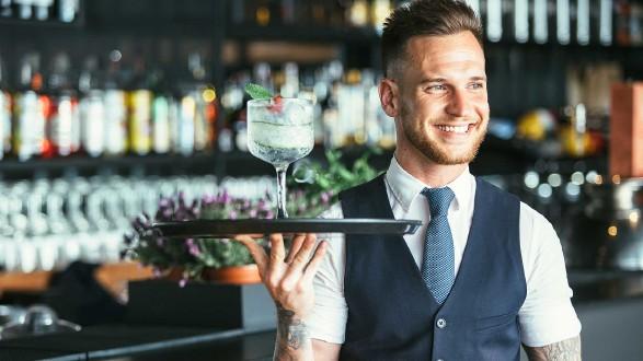 Freundlicher Kellner mit Tablett serviert ein Getränk © click_and_photo, stock.adobe.com