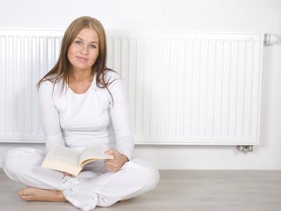 Frau sitzt vorm Heizkörper und liest ein Buch. © Katarzyna Leszczynsk, Fotolia