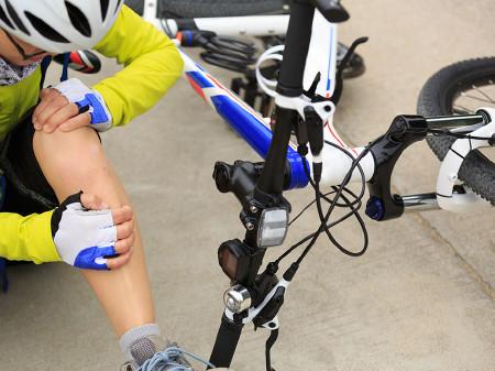 Radfahrer sitzt verletzt am Boden neben Fahrrad. © lzf, AdobeStock