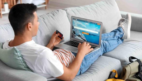 Mann auf der Couch bucht einen Flug online © Pixel-Shot, stock.adobe.com