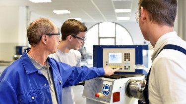 Ein Arbeiter zeigt zwei jungen Kollegen eine Maschine. © stock.adobe.com, industrieblick