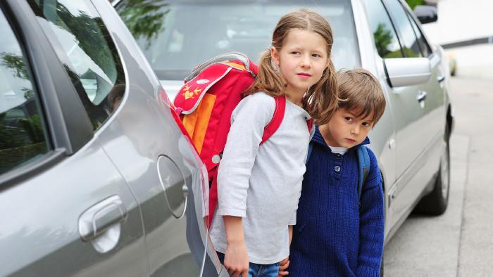 Zwei Schulkinder stehen zwischen Autos auf der Straße. © photophonie - stock.adobe.com, AK Stmk