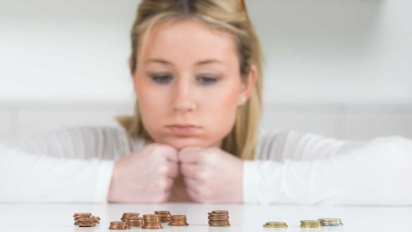 Frau mit traurigem Blick auf Geldmünzen © Picture-Factory, stock.adobe.com