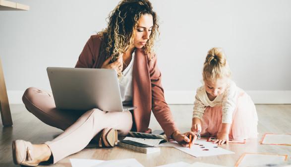 Frau spielt mit Tochter, während sie ihren Laptop auf dem Schoß hat. © Mariia Korneeva, stock.adobe.com