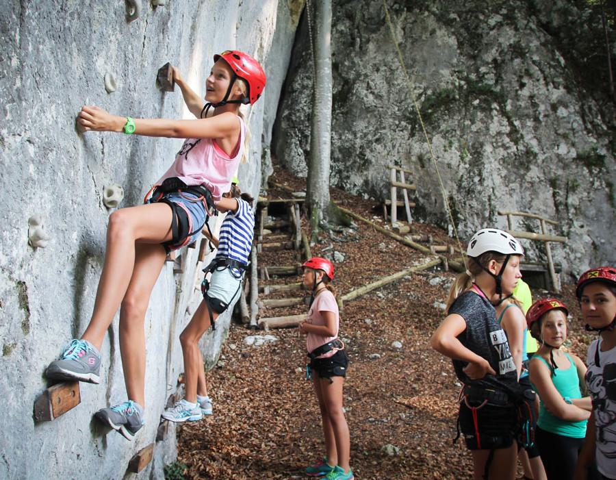 Kinder klettern an einer Felswand. © kuume, Ferienhort