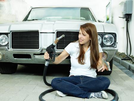 Frau sitzt vor dem Auto am Boden mit Zapfhahn und Geld in den Händen. © Karin & Uwe Annas, AdobeStock