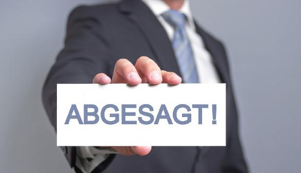 """Mann mit Schild """"Abgesagt"""" © Jamrooferpix, stock.adobe.com"""