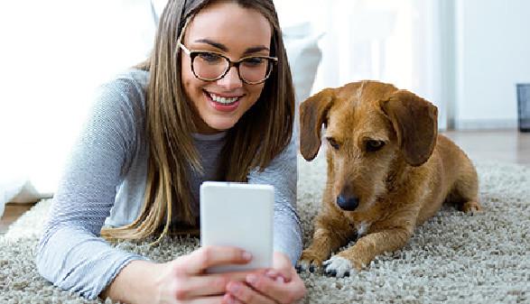 Junge Frau mit Hund und Smartphone © nenetus, Fotolia