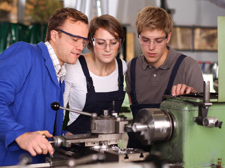 Zwei Lehrlinge stehen mit dem Lehrherrn bei einer Maschine und lassen sich etwas zeigen. © Fotolia.com/ehrenberg, AK Stmk