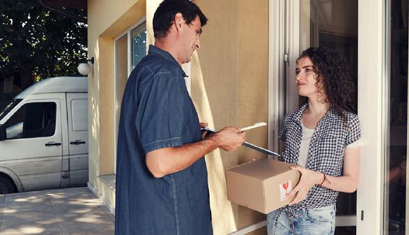 Zusteller übergibt Frau ein Paket. © Dariya Angelova, AdobeStock