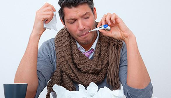 Mitarbeiter mit Fieberthermometer im Mund fühlt sich krank. © detailblick, Fotolia.com