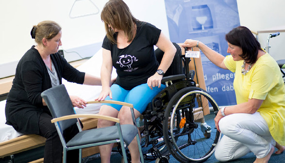 Auf der Pflegemesse wird das richtige Heben aus dem Rollstuhl gezeigt. © Graf, AK Stmk