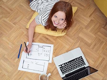 Lächelnde Frau zeichnet Skizze von Wohnung. © contrastwerkstatt, AK