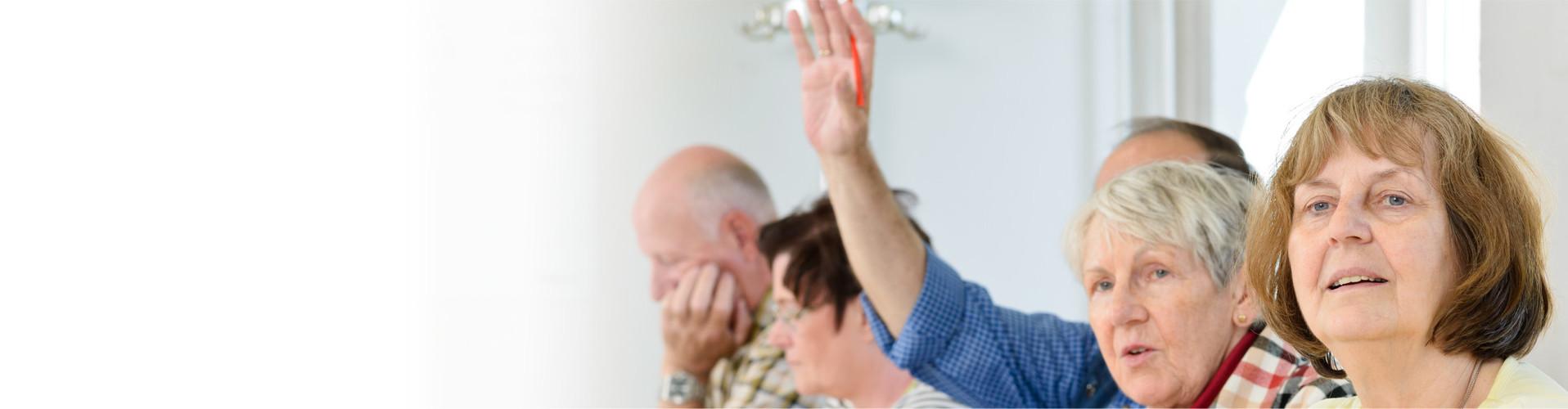 Drei Frauen und zwei Männer sitzen in einem Klassenzimmer, ein Mann hebt die Hand © Claudia Paulussen, stock.adobe.com