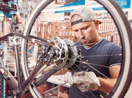 Mann repariert Fahrrad. © Aleksey, stock.adobe.com