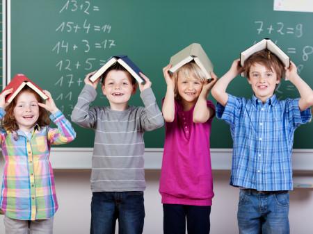 Kinder vor der Tafel mit Büchern am Kopf © fotolia/contrastwerkstatt, AK Stmk